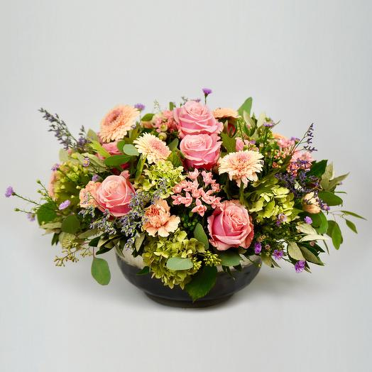 A generous, classic arrangement of flowers and green foliage in a meta