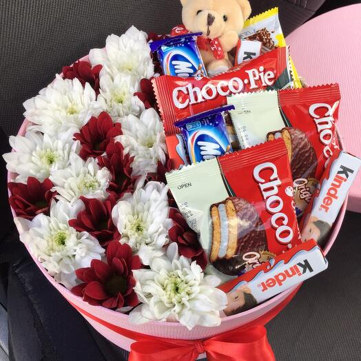 Teddy bear in sweets and flowers