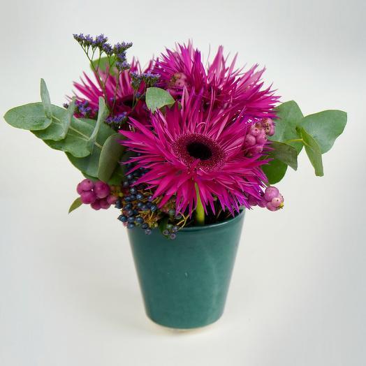 A sweet arrangement of gerbera and foliage in a pot