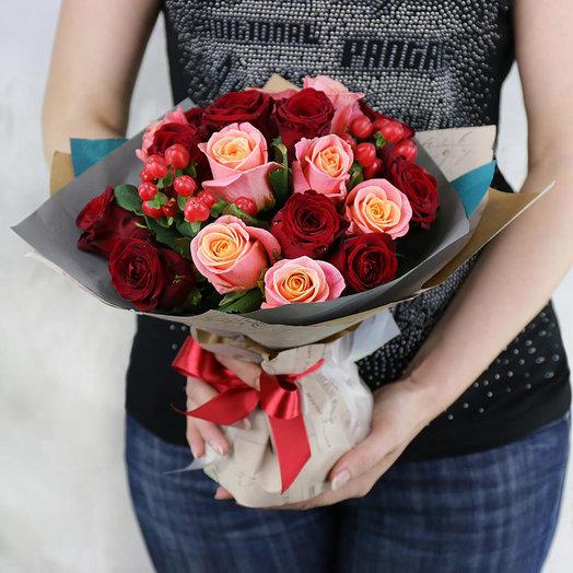 Яркий букет из красных и розовых роз с гиперикумом в упаковке