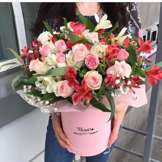 A delicate composition of alstroemeria and roses in a hatbox